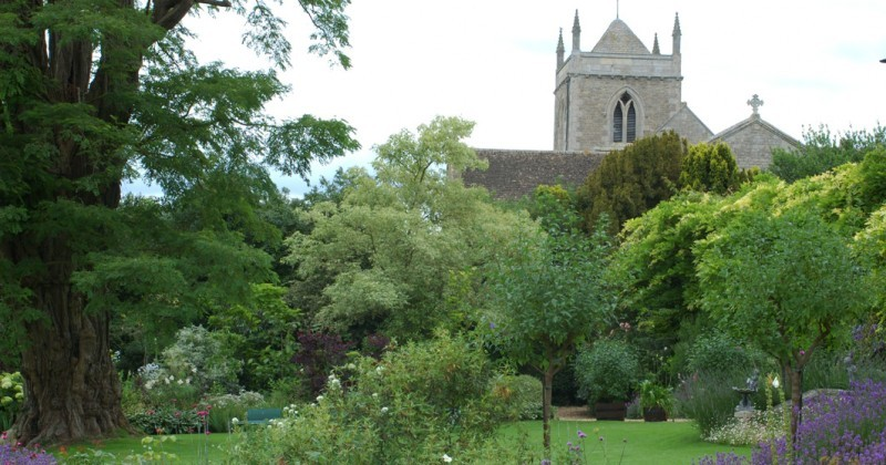 Sudborough garden view with church in the background. Lush green lawn surrounded by small trees and plants, with a large old tre on the left side.