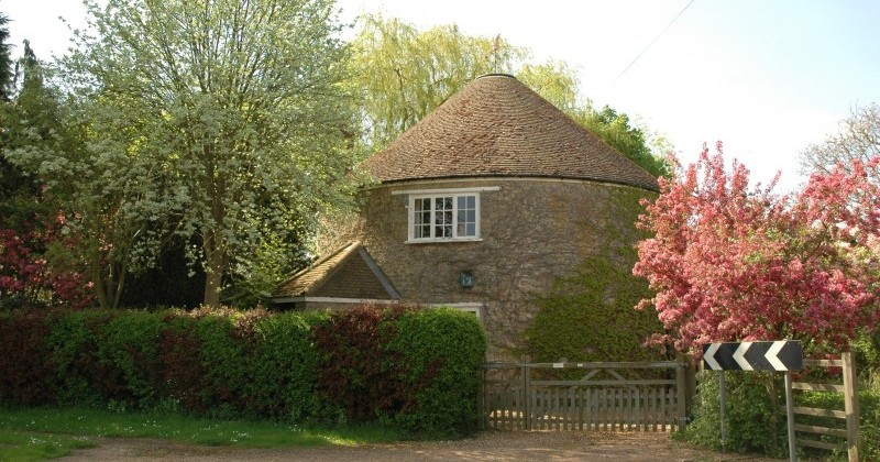 Sudborough round house, a cylindrical brick building with one window showing and a conical tiled roof, set behind a hedgerow and some small trees. Its a bright sunny day