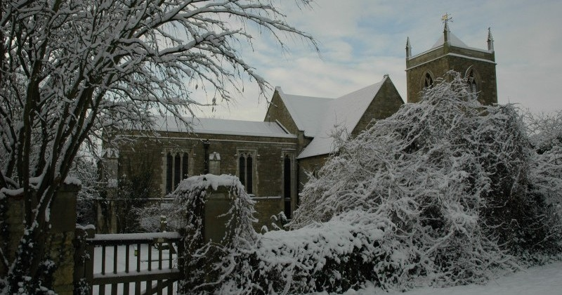 View from path outside of Sudborough Parish Church in winter. Gate, wall, bushes, trees and Church all covered in an inch of snow.