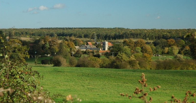 View across and down to Sudborough village from a nearby green field which rises up from the village. Early Autumn foliage beginning to turn and with near clear blue skies.